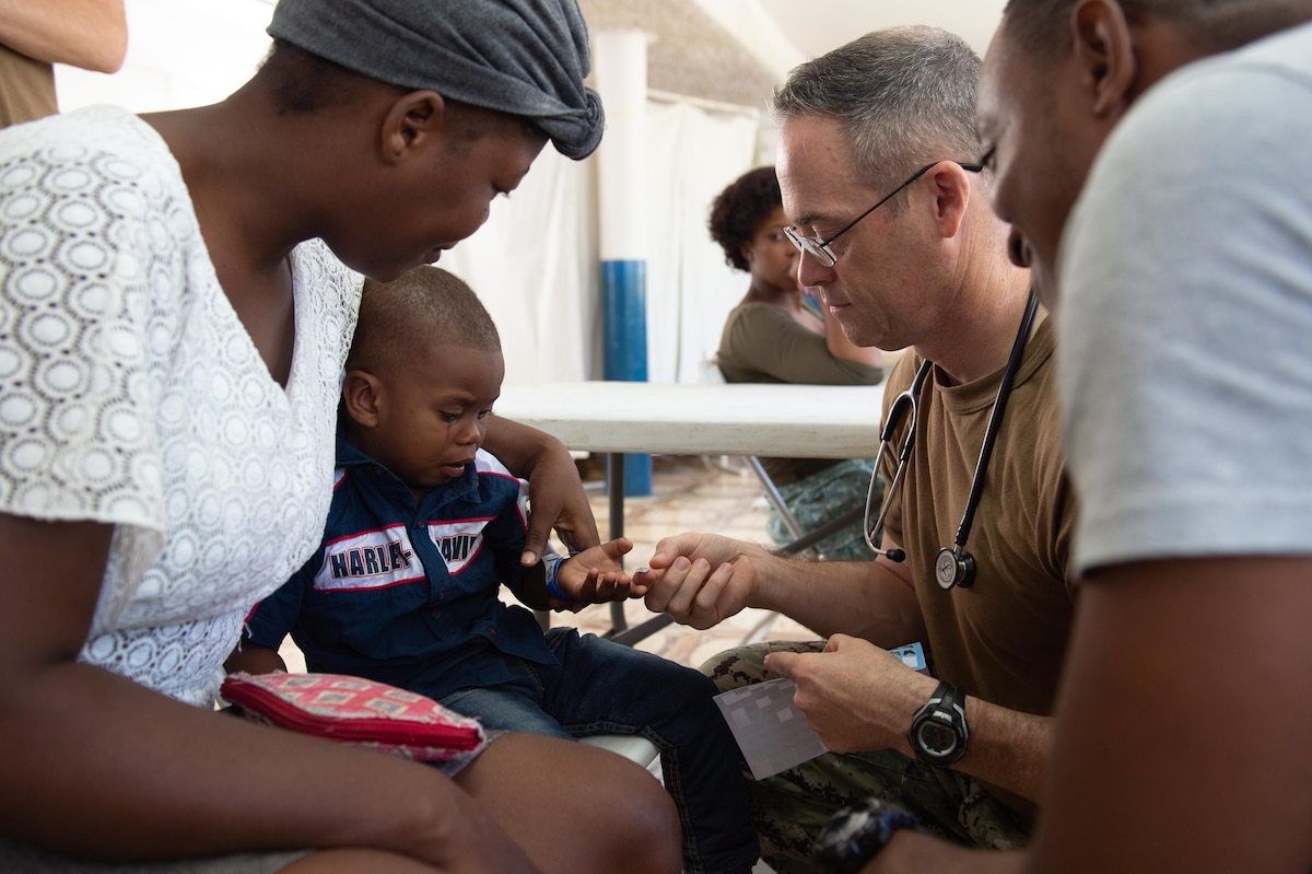 U.S. Navy Capt. Michael Sullivan, a pediatrician assigned to the hospital ship USNS Comfort (T-AH 20), gives a sticker to a two-year-old boy after examining his skin infection at a temporary medical treatment site in Port-Au-Prince, Haiti Nov. 6, 2019.
