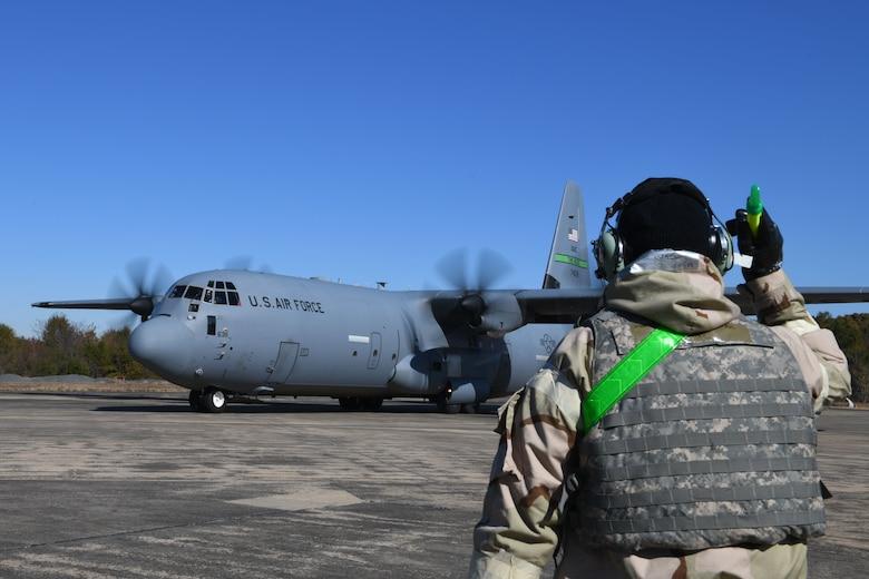 An Airman marshals a C-130J plane