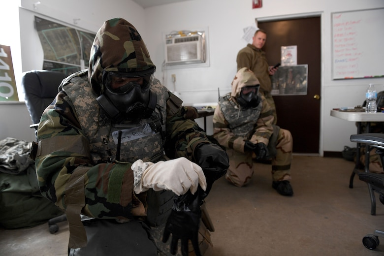 An Airman puts on gloves