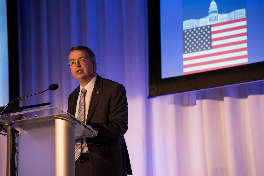 Deputy Defense Secretary  David L. Norquist speaks at a lectern.