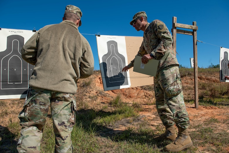 A German Armed Forces Proficiency Badge (GAFPB) competition proctor, right, reviews a participant's target at Fort Jackson, South Carolina, Nov. 9, 2019.