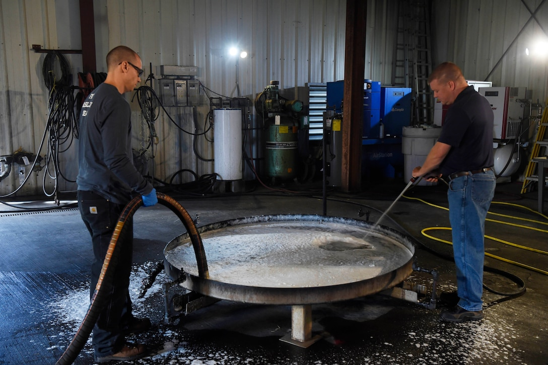 Researchers use hoses to clean firefighting foam out of container.