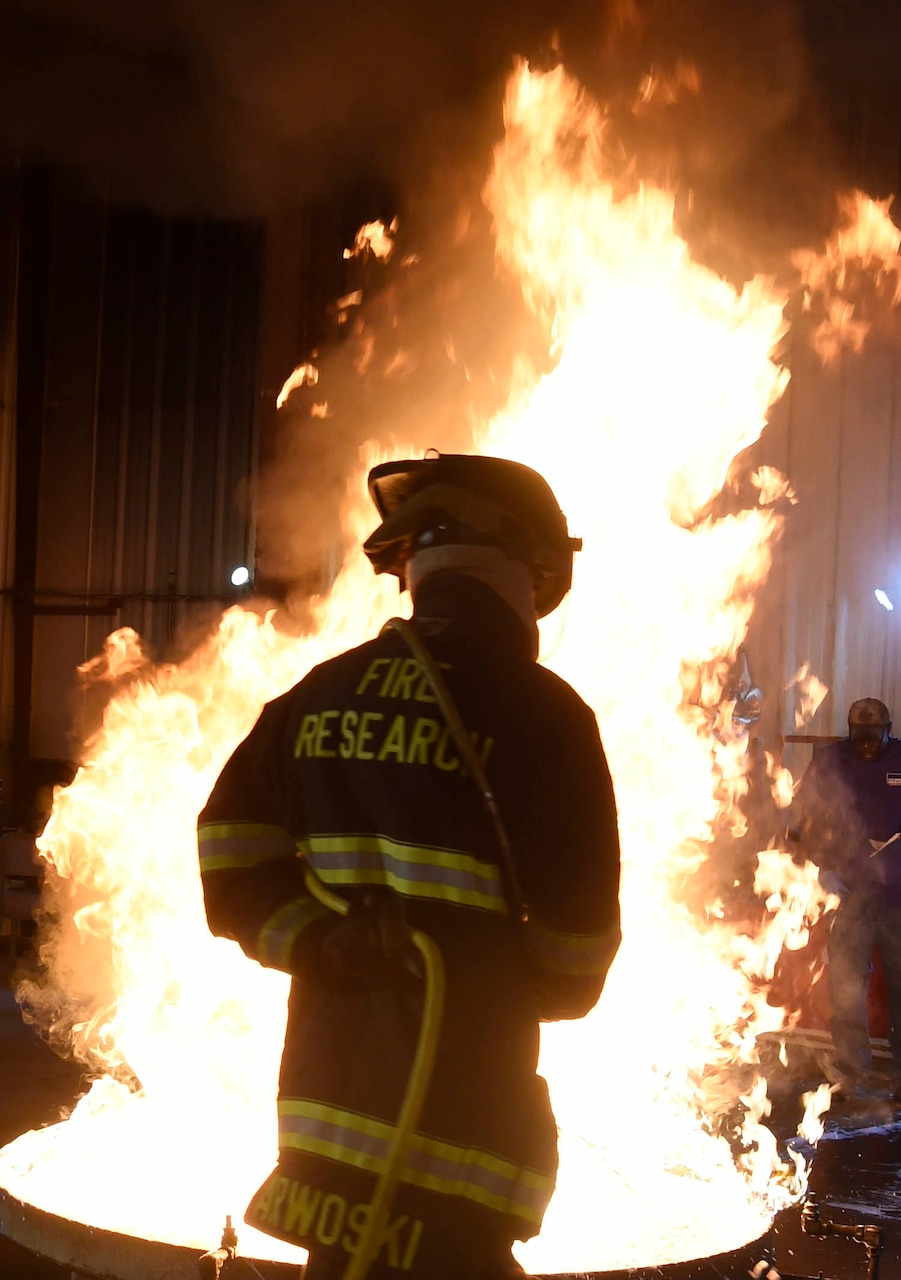 A person wearing fire protection gear sprays foam on a fire in a 28-square-foot container.