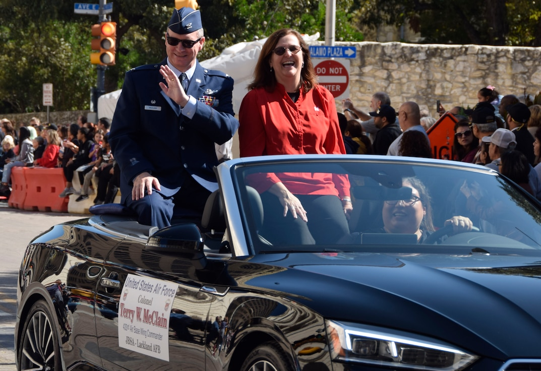 Col. Terry W. McClain, 433rd Airlift Wing commander and his spouse, Marci, interact with the spectators during the U.S. Military Veteran's Parade Association's parade through downtown San Antonio, Texas, Nov. 9, 2019. (U.S. Air Force photo by Staff Sgt. Lauren M. Snyder)