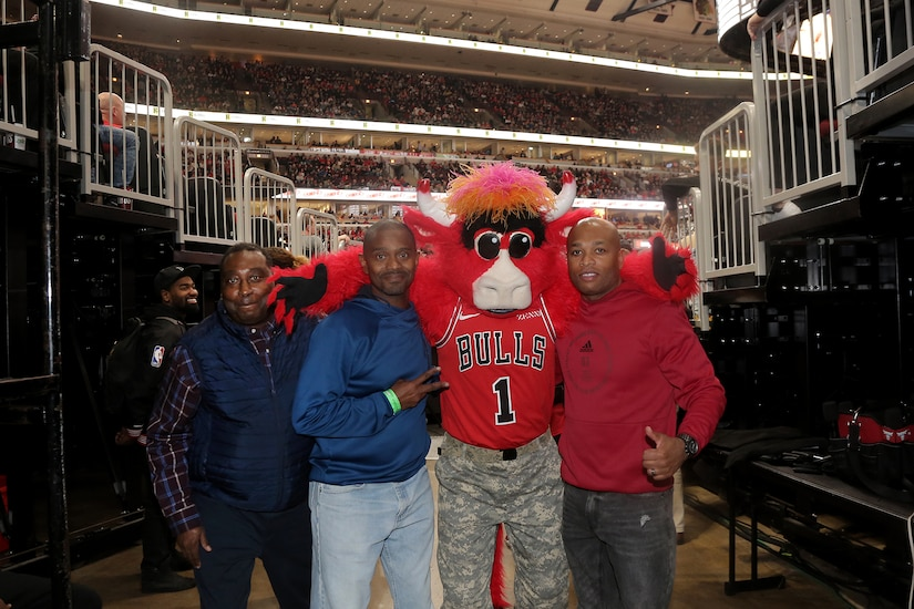 (From left to right) Chief Warrant Officer 3 William Brinston, Chief Warrant Officer 4 Tilmon Wooden, and Master Sgt. Laroy Warren pause for a photo with Benny the Bull, Chicago Bulls mascot, at a military appreciation game at the United Center in Chicago, November 9, 2019.