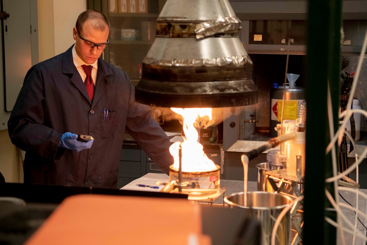 A chemist holds a stopwatch as he times an experiment of a small fire in a lab.