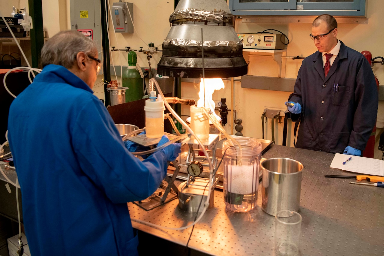 A chemist pours foam on a small fire as another chemist holds a stopwatch.