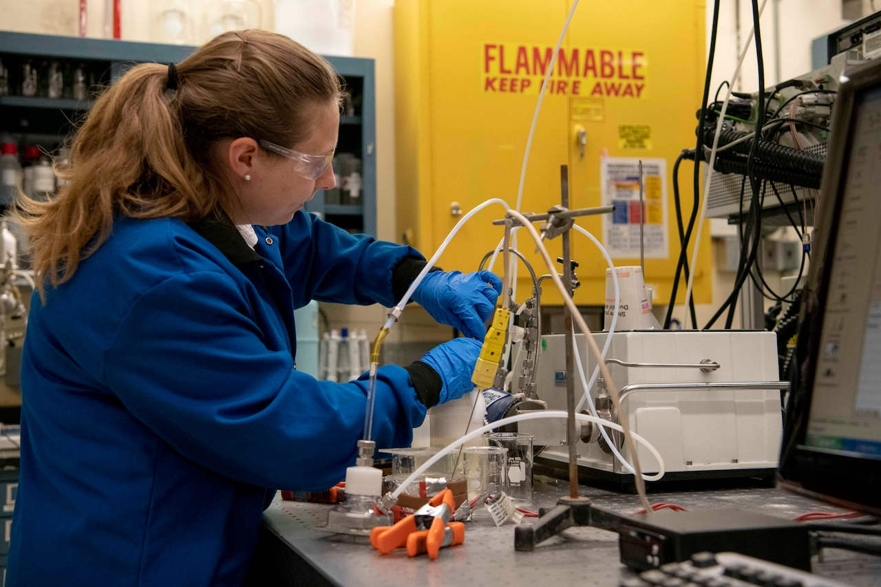 A chemist in a lab begins filling a plastic container with foam.