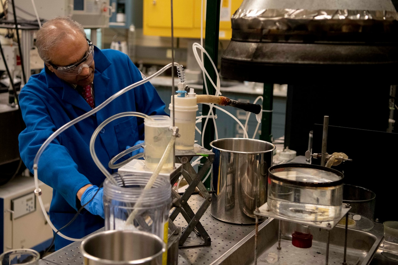 A chemist in a lab begins filling a metal container with foam.