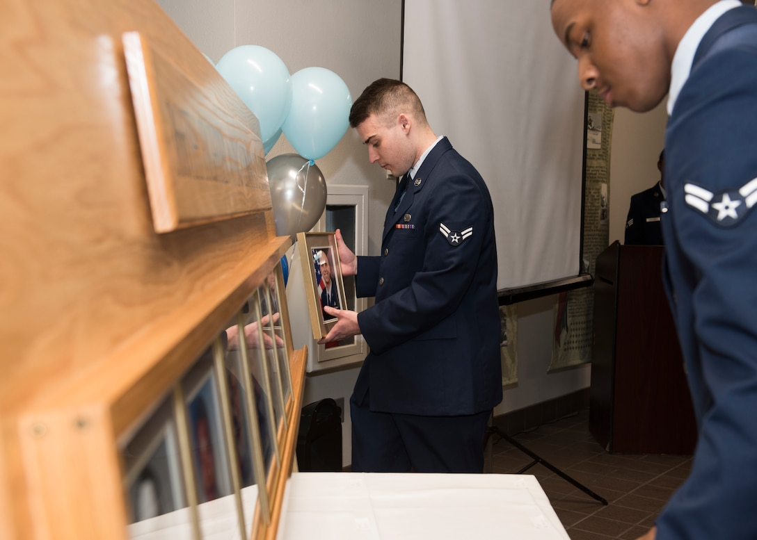 Two Airmen place plaques into a wooden fixture during a ceremony, Nov. 11, 2019, at Mountain Home Air Force Base, Idaho. The fixture is part of a legacy wall within the 366th Fighter Wing used to document and honor prior command chiefs. (U.S. Air Force photo by Senior Airman Tyrell Hall)