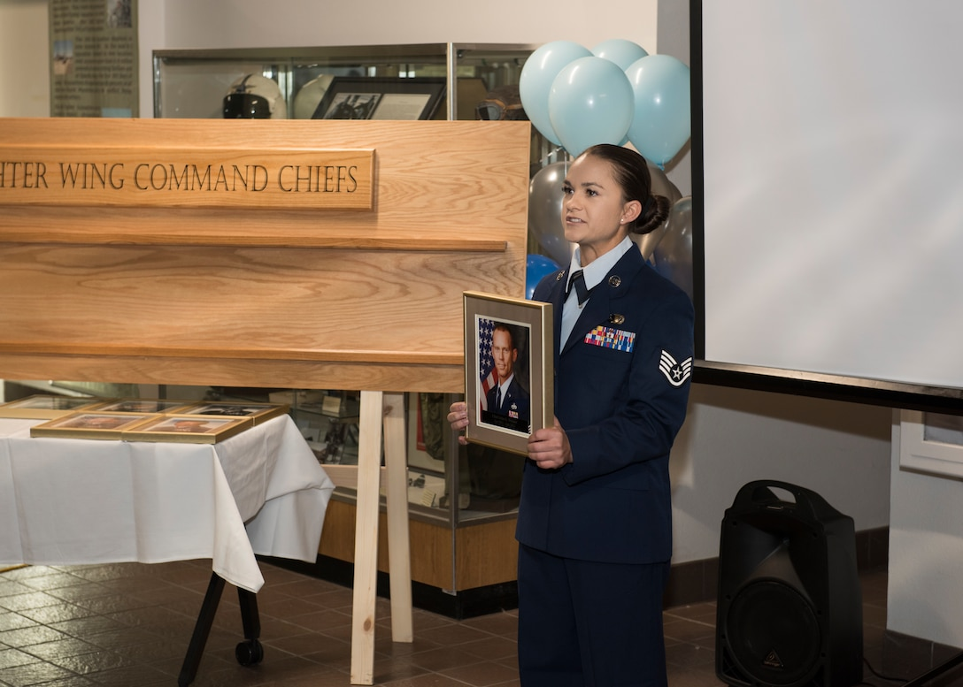 Staff Sgt. Alexandra Christofferson, 366th Force Support Squadron NCO in charge of outbound assignments, reads a biography for retired Chief Master Sgt. John Weimer, former 366th FW command chief at a ceremony, Nov. 11, 2019, at Mountain Home Air Force Base, Idaho. The ceremony entails honoring MHAFB's top enlisted leaders who've served in the 366th FW as senior enlisted advisors. (U.S. Air Force photo by Senior Airman Tyrell Hall)