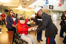 Major Ernest Robinson, Headquarters Company commanding officer and Base Operations officer from Marine Corps Logistics Base Barstow, hands the first piece of birthday cake to the oldest Marine, Arthur Monde, at the tender age of 94, present during the U.S. Marine Corps' birthday celebration at the Veterans Home of  California - Barstow, Calif., Nov. 8. Traditionally the first piece of cake is served to the oldest Marine then the youngest Marine present at the ceremony. Youngest Marine present at the ceremony was 19-year old Lance Cpl. Noah Avila, data systems administrator for MCLB Barstow.