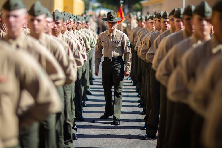 A Marine walks in between a large group of Marines standing in rows.