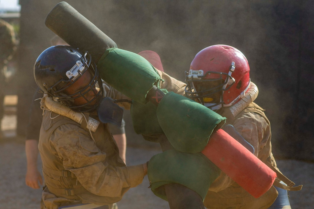 Two Marine Corps recruits fight each other using pugil sticks.