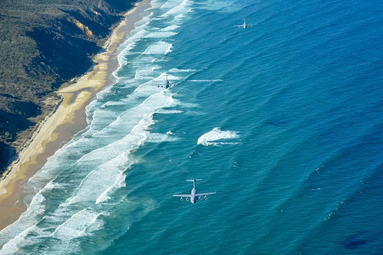 Three planes fly over a beach.