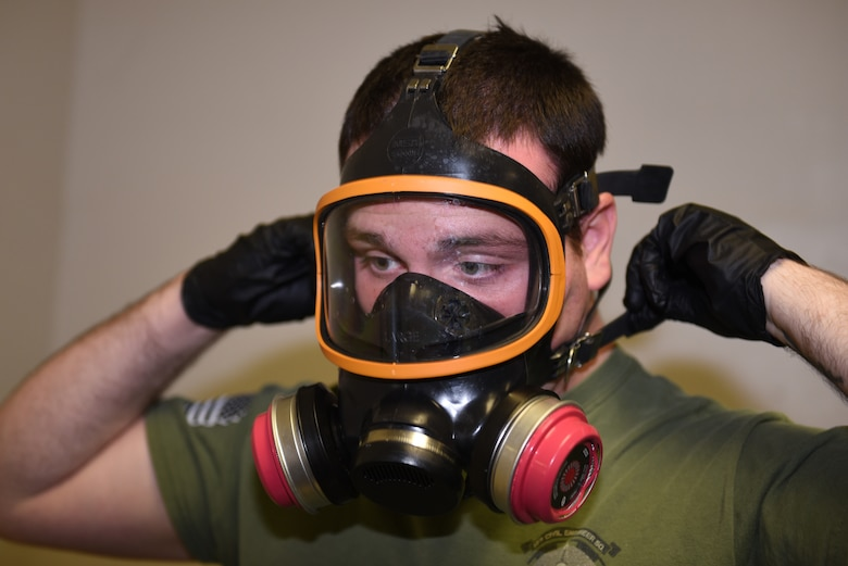 U.S. Air Force Senior Airman David De Alva, 60th Civil Engineer Squadron pest management technician, puts on his gas mask to check if the filters are working properly Nov. 8, 2019, at Travis Air Force Base, California. De Alva uses the mask for fumigating jobs and spraying down Travis aircraft after they've returned from missions around the world. (U.S. Air Force photo by Airman 1st Class Cameron Otte)
