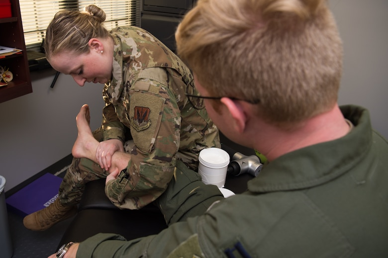 U.S. Air Force Capt. Michelle Jilek, 633rd Medical Operations Squadron physical therapist, examines Capt. Breck Stewart, 71st Fighter Squadron T-38 Talon pilot, at Joint Base Langley Eustis, Virginia, Nov. 13, 2019.