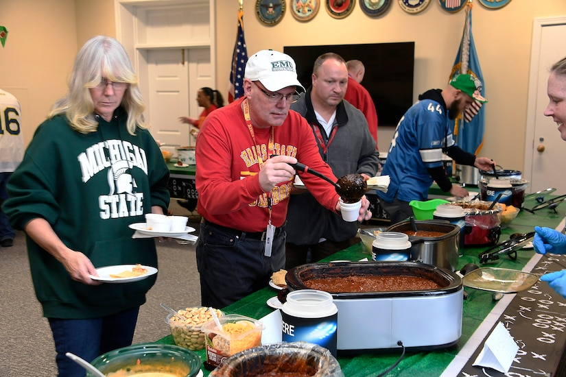 People fill their plates in a pot luck line.