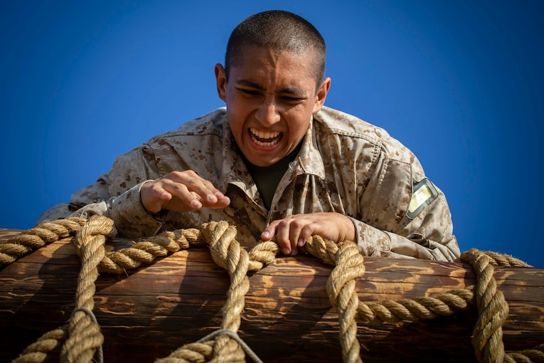 A Marine Corps recruit climbs over a cargo net.