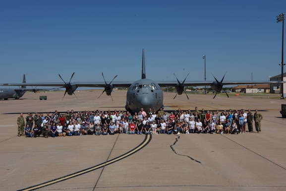 Dyess Airmen and spouses pose in front of a C-130J Super Hercules at Dyess Air Force Base, Texas, Oct. 5, 2019. The 317th Airlift Wing Spouse Day allowed spouses to witness what their spouse does and how they contribute to the mission. (U.S. Air Force photo by Airman 1st Class Colin Hollowell)