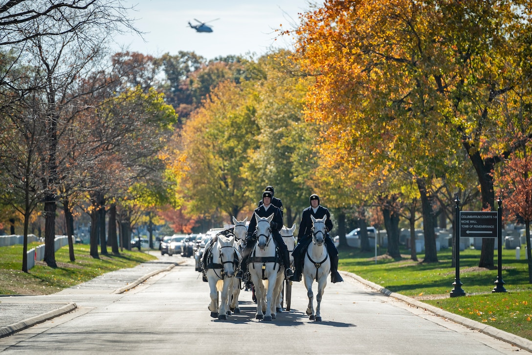 Service members on horses travel down a road.