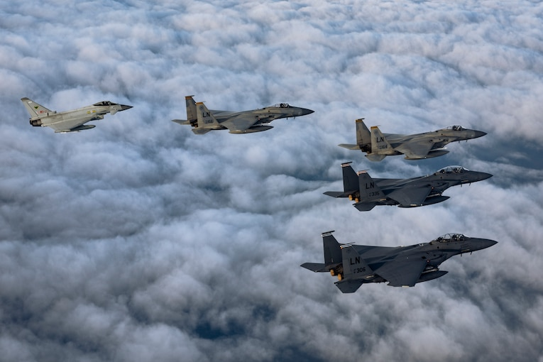 Five military aircraft fly in formation.