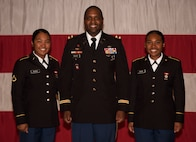 Chief Warrant Officer 5 Dean Registe, U.S. Army Engineer School Regimental Chief Warrant Officer, poses with his daughters, Pvt. Malia Registe, right, and Pfc. Marlina Registe, after their graduation from Army basic training at Fort Leonard Wood, Mo., Nov. 14, 2019.