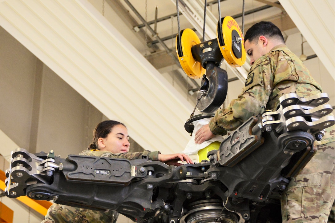 Two airman work on a helicopter.