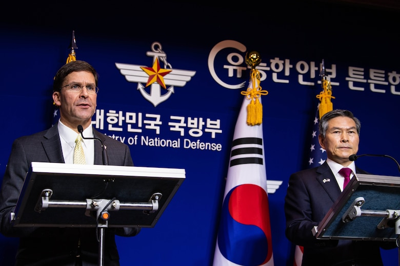 Two defense leaders stand  and answer questions.