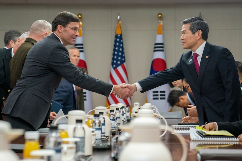Two men shake hands over a large table.