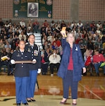Dr. Isabell Clayton (right), Cole High School principal, holds the Purple Heart medal of Lt. Col. Robert G. Cole for parents, teachers, students and World War II veterans who were present to see at a Veterans Day observance at the Cole High School gymnasium Nov. 8. The Purple Heart medal, which was awarded to Cole posthumously 75 years ago, made its way to the school named after him because of the efforts of Lisa Ludwig, a Long Island, New York resident who found and purchased the medal at a gun show and donated it to the school.
