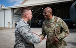 U.S. Air Force Gen. CQ Brown, Jr., Pacific Air Forces commander, coins Airman 1st Class Tucker Heyduk, 18th Civil Engineer Squadron barrier maintenance technician, during a tour at Kadena Air Base, Japan, Nov. 12, 2019. During the tour, Brown coined Airmen from different units as a way of thanks and recognition of their superior performance.