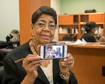 Lucy Richardson shows a photo of her friends attending a party at the beauty salon at Nov. 4 Joint Base San Antonio-Randolph AAFES beauty salon. The celebration recognizing Richardson for her service at the salon for 50 years was Aug 30.