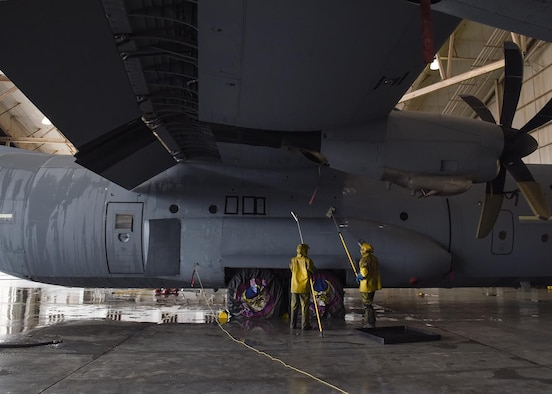 Photo shows Airmen, dressed in yellow protective gear, wetting sponges to clean a C-130J Super Hercules aircraft.