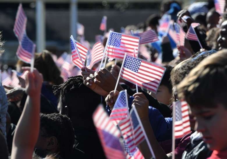 Students at Jeff Davis Elementary School wave U.S. flags during a Veterans Day celebration in Biloxi, Mississippi, Nov. 15, 2019. During the event, students also recited the Pledge of Allegiance. Keesler Air Force Base leadership and base personnel attended the event. (U.S. Air Force photo by Kemberly Groue)