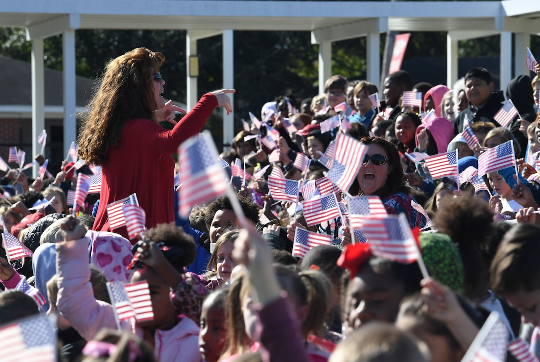 Marsha Gaines, Jeff Davis Elementary School music teacher, leads students with singing patriotic songs during a Veterans Day celebration in Biloxi, Mississippi, Nov. 15, 2019. During the event, students also recited the Pledge of Allegiance. Keesler Air Force Base leadership and base personnel attended the event. (U.S. Air Force photo by Kemberly Groue)