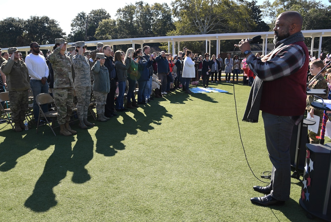 Keesler Air Force Base personnel and family members pay their respects during the singing of the national anthem by U.S. Navy veteran Bryant White during the Jeff Davis Elementary School Veterans Day celebration in Biloxi, Mississippi, Nov. 15, 2019. During the event, students also recited the Pledge of Allegiance. Keesler Air Force Base leadership and base personnel attended the event. (U.S. Air Force photo by Kemberly Groue)