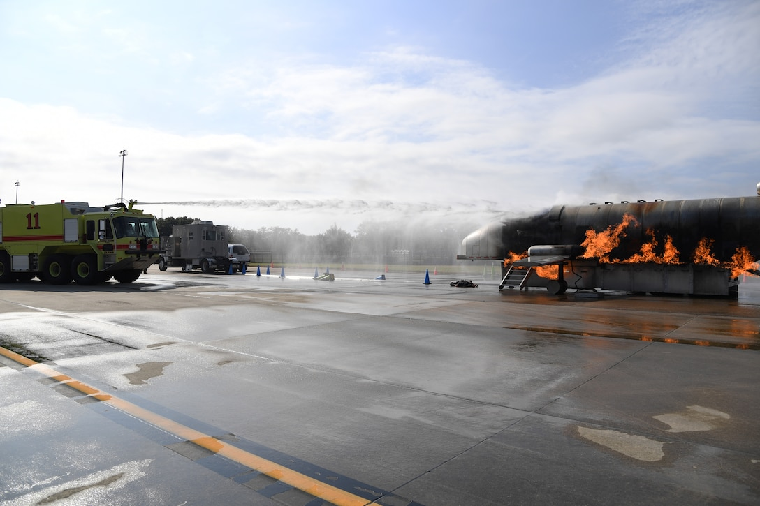 Keesler firefighters operate a fire truck to extinguish a fire on a mock C-123 training device during an aircraft rescue fire fighting training exercise at Keesler Air Force Base, Mississippi, Nov. 6, 2019. The five-day joint agency training allowed the Keesler Fire Department and the Gulfport Combat Readiness Training Center Fire Department to meet the semi-annual training requirement to practice aircraft rescue and live fire training evolutions. (U.S. Air Force photo by Kemberly Groue)