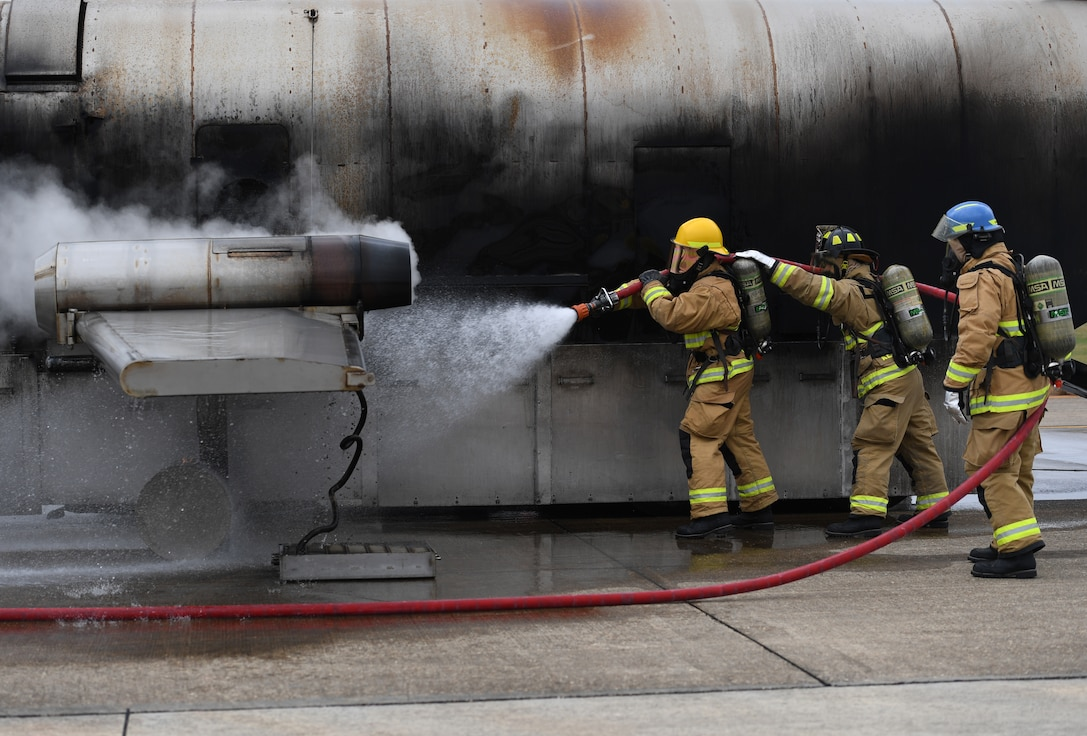 U.S. Air Force Airman Mason Songy, 209th Civil Engineer Squadron firefighter, Gulfport Combat Readiness Training Center Fire Department, Mississippi, and James Pettus and Guy Chadwick, 81st Infrastructure Division firefighters, use a hand-held hose to extinguish a fire on a mock C-123 training device during an aircraft rescue fire fighting training exercise at Keesler Air Force Base, Mississippi, Nov. 8, 2019. The five-day joint agency training allowed the Keesler Fire Department and the Gulfport Combat Readiness Training Center Fire Department to meet the semi-annual training requirement to practice aircraft rescue and live fire training evolutions. (U.S. Air Force photo by Kemberly Groue)