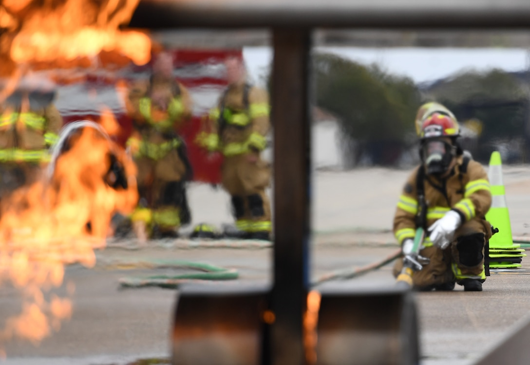 Keesler firefighters use a hand-held hose to extinguish a fire on a mock C-123 training device during an aircraft rescue fire fighting training exercise at Keesler Air Force Base, Mississippi, Nov. 8, 2019. The five-day joint agency training allowed the Keesler Fire Department and the Gulfport Combat Readiness Training Center Fire Department to meet the semi-annual training requirement to practice aircraft rescue and live fire training evolutions. (U.S. Air Force photo by Kemberly Groue)