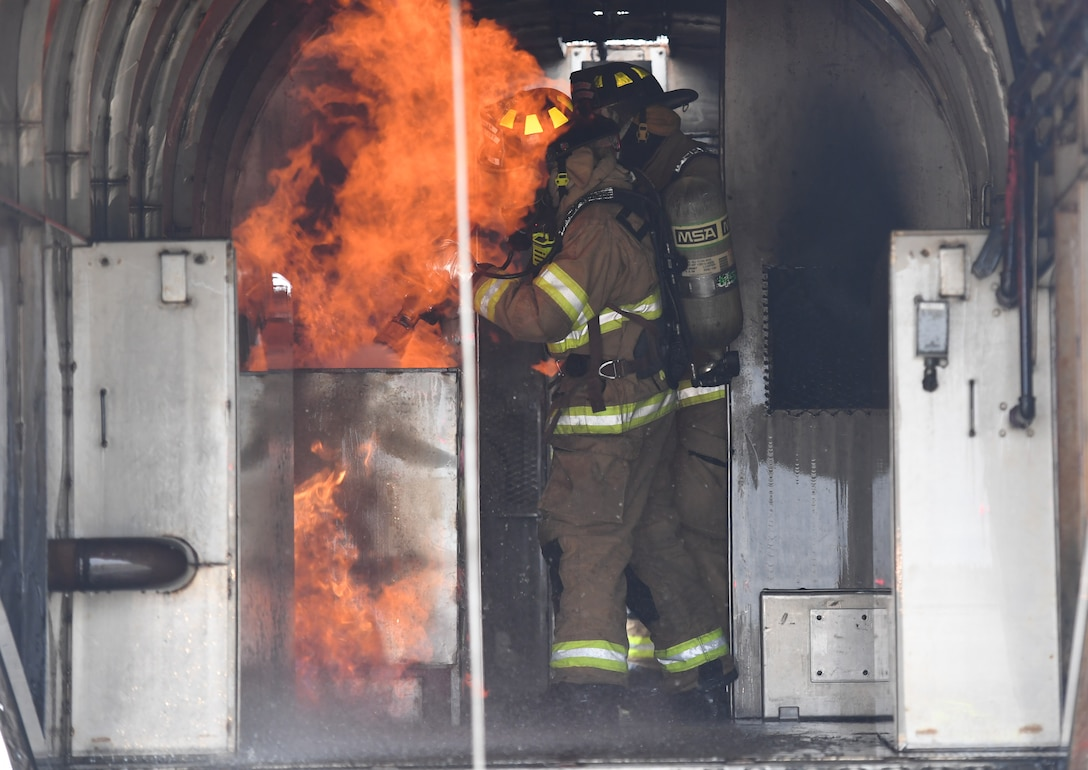Cole Ballard and Seth Corn, 81st Infrastructure Division firefighters, use a hand-held hose to extinguish a fire inside a mock C-123 training device during an aircraft rescue fire fighting training exercise at Keesler Air Force Base, Mississippi, Nov. 8, 2019. The five-day joint agency training allowed the Keesler Fire Department and the Gulfport Combat Readiness Training Center Fire Department to meet the semi-annual training requirement to practice aircraft rescue and live fire training evolutions. (U.S. Air Force photo by Kemberly Groue)