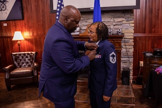 Retired U.S. Air Force Senior Master Sgt. Adrienne Smith is presented a meritorious service medal by retired Chief Master Sgt. Michael Brown during her retirement ceremony at the U.S. Army Transportation Museum. Smith retired after nearly 34 years of service in the U.S. Air Force Reserves. (DOD photo by Mass Communication Specialist 3rd Class Michael Redd/RELEASED)