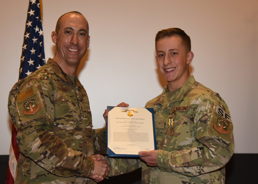 Airman 1st Class Christopher Horton, 790th MSFS Defender, receives an Air Force Commendation Award from 90th Security Forces Group Commander Col. Damian Schlussel during a ceremony Nov. 15, 2019, at the Base Theater on F. E. Warren Air Force Base, Wyo. Horton received the commendation for actions taken in rescuing a family in danger of a house fire Nov. 7 in Dix, Nebraska. Horton was recognized alongside his teammate, Airman 1st Class Christian Reid. (Air Force photo by Glenn S. Robertson)