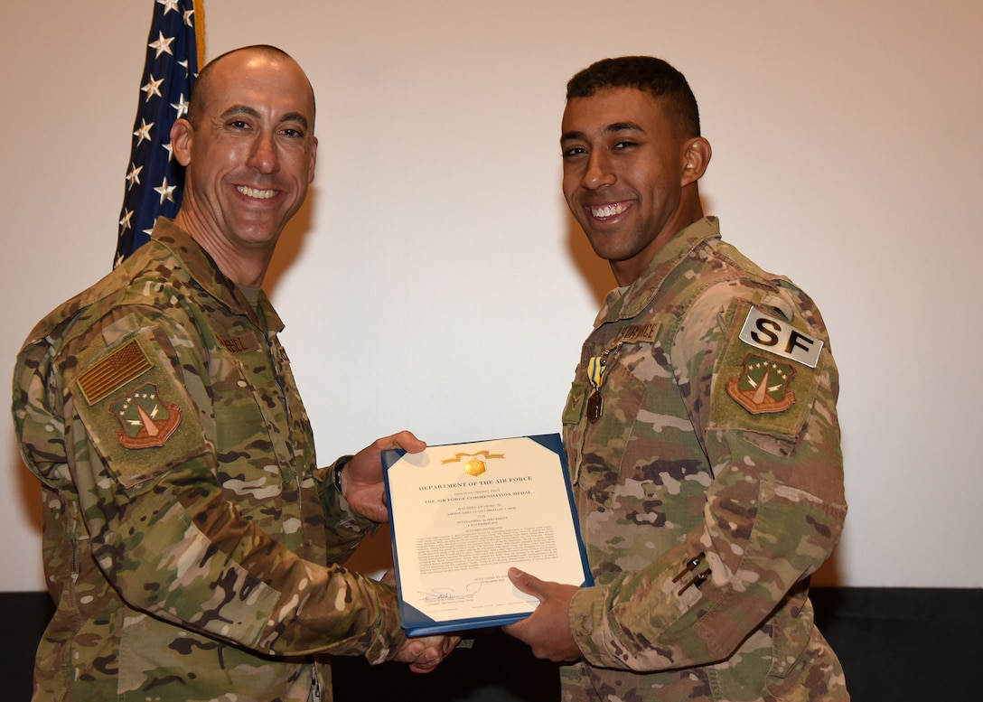 Airman 1st Class Christian Reid, 790th MSFS Defender, receives an Air Force Commendation Award from 90th Security Forces Group Commander Col. Damian Schlussel during a ceremony Nov. 15, 2019, at the Base Theater on F. E. Warren Air Force Base, Wyo. Horton received the commendation for actions taken in rescuing a family in danger of a house fire Nov. 7 in Dix, Nebraska. Reid was recognized alongside his teammate, Airman 1st Class Christopher Horton. (Air Force photo by Glenn S. Robertson)