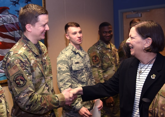 U.S. Air Force 2nd Lt. Kiefer Luth, 334th Training Squadron student, shakes hands with his mother, Tamera Luth, during an Airfield Operations Officer Course graduation inside the Dempsey Conference Room inside Cody Hall at Keesler Air Force Base, Mississippi, Nov. 8, 2019. Luth recently completed the course and graduated in the room dedicated to his grandfather, retired Col. Derrel Dempsey. The room was dedicated to Dempsey to honor his military accomplishments. (U.S. Air Force photo by Airman Seth Haddix)
