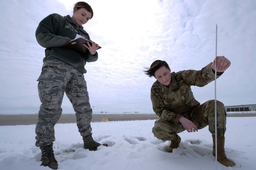 Two people measure snow.