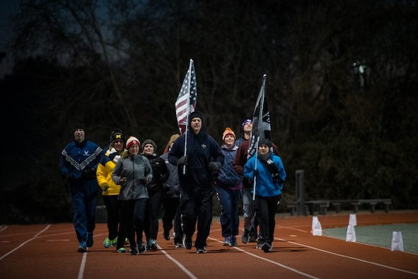 U.S. Air Force Reserve Citizen Airmen from the 932nd Airlift Wing keep the American and POW/MIA flags moving around the James Gym track during the 10th Annual Air Force Sergeants Association POW/MIA Vigil Run, Nov. 15, 2019, Scott Air Force Base, Illinois. The run/walk honors all POW/MIAs as the flag is carried for 24 hours.  The cold temperatures were visible in the cold breaths and frost on the flags but that didn't stop the flags from continually moving.   (U.S. Air Force photo by Christopher Parr)
