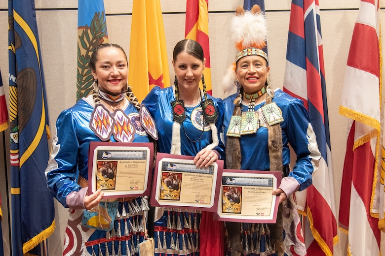 Three members of the Native American Women Warriors stand together with their certificates of appreciation at the National American Indian Heritage Month observance at Redstone Arsenal, Alabama, Nov. 13, 2019. From left to right: Army veteran Keshon Smith; Marine Corps veteran Carrie Lewis; and Army veteran Mitchelene BigMan, president and founder of NAWW. The observance was organized by Huntsville Center's Equal Employment Opportunity office in coordination with Team Redstone and the U.S. Army Aviation and Missile Command. The Native American Women Warriors are an all-female group of Native American veterans who started as a color guard but have since grown and branched out as advocates for Native American women veterans in areas such as health, education and employment. The members make appearances at various events around the country, serving as motivational and keynote speakers, performing tribal dances, and fulfilling the role of color guard representing all branches of the U.S. military.