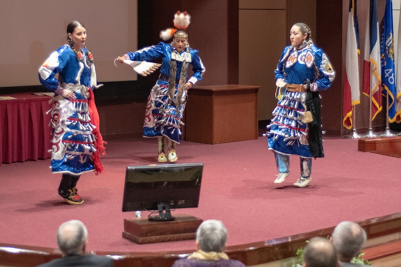 Three members of the Native American Women Warriors perform a tribal dance for attendees of the National American Indian Heritage Month observance at Redstone Arsenal, Alabama, Nov. 13, 2019. Pictured are Army veteran Keshon Smith, right; Marine Corps veteran Carrie Lewis, left; and Army veteran Mitchelene BigMan, center, president and founder of NAWW. The observance was organized by Huntsville Center's Equal Employment Opportunity office in coordination with Team Redstone and the U.S. Army Aviation and Missile Command. The Native American Women Warriors are an all-female group of Native American veterans who started as a color guard but have since grown and branched out as advocates for Native American women veterans in areas such as health, education and employment. The members make appearances at various events around the country, serving as motivational and keynote speakers, performing tribal dances, and fulfilling the role of color guard representing all branches of the U.S. military.