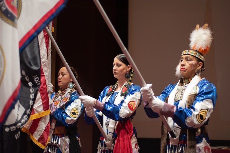 """Three members of the Native American Women Warriors render honors during a vocal performance of """"The Star-Spangled Banner"""" at the National American Indian Heritage Month observance at Redstone Arsenal, Alabama, Nov. 13, 2019. From left: Army veteran Keshon Smith; Marine Corps veteran Carrie Lewis; and Army veteran Mitchelene BigMan, president and founder of NAWW. The observance was organized by Huntsville Center's Equal Employment Opportunity office in coordination with Team Redstone and the U.S. Army Aviation and Missile Command. The Native American Women Warriors are an all-female group of Native American veterans who started as a color guard but have since grown and branched out as advocates for Native American women veterans in areas such as health, education and employment. The members make appearances at various events around the country, serving as motivational and keynote speakers, performing tribal dances, and fulfilling the role of color guard representing all branches of the U.S. military."""
